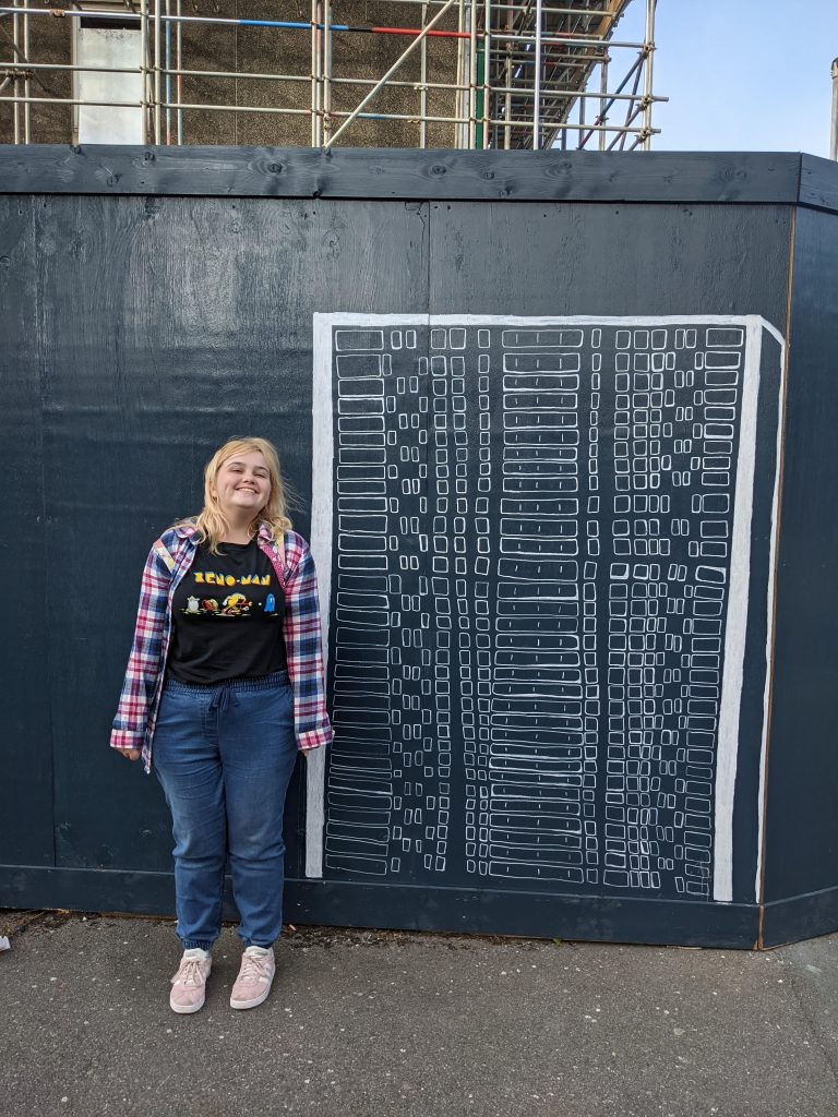 Artist Skyla Swan stands next to her artwork on a construction site hoarding